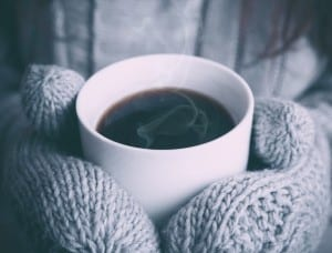 warm cup of coffee with gray mittens
